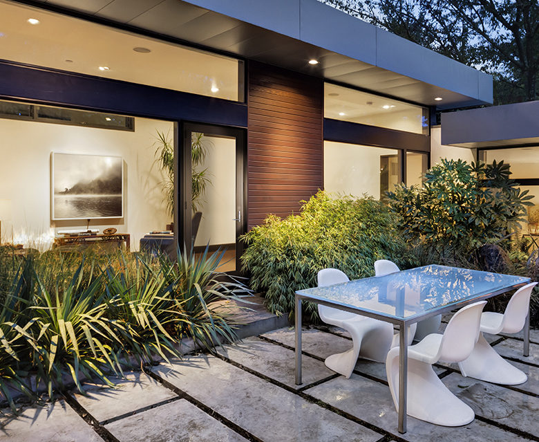 Courtyard of modern home at twilight with interior views of home
